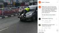 Seorang polisi nampak berpegangan pada bagian depan mobil yang sedang melaju di Pasar Minggu. (Instagram @jktinfo)