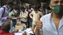 Pelancong mengacungkan jempol setelah memberikan sampel untuk uji COVID-19 di luar stasiun kereta di Bengaluru, Minggu (11/4/2021). India melaporkan lonjakan infeksi, yang menurut para ahli disebabkan oleh mengabaikan aturan jaga jarak sosial serta mengenakan masker di ruang publik. (AP/Aijaz Rahi)