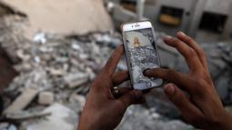 Seorang gamer Suriah menemukan Pokemon di antara reruntuhan di daerah konflik Suriah, Damaskus (23/7). (AFP PHOTO / Sameer Al-Doumy)