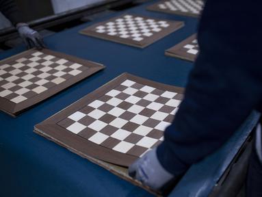 """Seorang karyawan Rechapados Ferrer membuat papan catur di La Garriga dekat Barcelona (5/3/2021). Penjualan pembuat papan catur Spanyol itu melonjak sejak ditampilkan di serial Netflix terkenal """"The Queen's Gambit"""". (AFP Photo/Josep Lago)"""