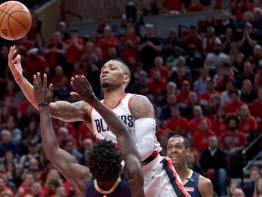 Aksi pemain Blazers, Damian Lillard melakukan tembakan melewati adangan pemain Pelicans, Jrue Holiday pada laga Playoffs game ke-2 NBA basketball di Moda Center, Portland, (17/4/2018). Pelicans menang 111-102. (AP/Craig Mitchelldyer)