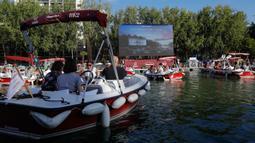 """Orang-orang menghadiri pemutaran film """"Le grand bain"""" pada hari pertama acara musim panas """"Paris-Plages"""" di La villette bassin, Paris, 18 Juli 2020. Paris menghadirkan sebuah terobosan baru dengan bioskop terapung lengkap dengan perahu yang tetap menjaga jarak sosial. (GEOFFROY VAN DER HASSELT/AFP)"""