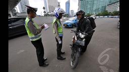 Petugas kepolisian menilang seorang pengendara motor yang menerobos Jalan MH Thamrin, Jakarta, Minggu (18/1/2015). (Liputan6.com/Miftahul Hayat)