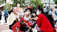 Pengunjung mengenakan masker guna melindungi diri dari virus corona berswafoto sebelum memasuki Tokyo Disneyland di Urayasu, dekat Tokyo, Rabu (1/7/2020). Tokyo Disneyland dibuka kembali untuk pertama kalinya dalam empat bulan setelah sempat ditutup karena penyebaran Covid-19. (AP/ Koji Sasahara)