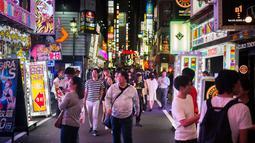 Orang-orang berjalan di distrik Shinjuku, Tokyo pada 22 September 2018. Shinjuku merupakan pusat perniagaan dan pemerintahan metropolitan sekaligus lokasi stasiun terbesar dan tersibuk di dunia. (AFP PHOTO / Martin BUREAU)