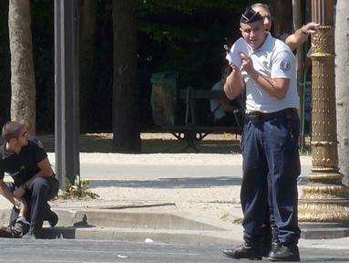Polisi militer Prancis berlutut dekat jasad seorang pria usai serangan terhadap van polisi di jalan Champs Elysees, Paris, Senin (19/6). Pelaku menggunakan mobil sedan putih untuk menabrakkan diri ke van polisi di jalanan kota. (Noemie Pfister via AP)