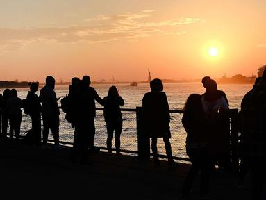 Sejumlah warga menikmati taman Brooklyn saat matahari terbenam di mana suhu mencapai hampir 70 derajat di New York City (21/2). Cuaca New York akan berubah kembali ke musim dingin dengan suhu yang diperkirakan 30 derajat. (AFP Photo/Spencer Platt)