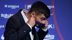 Penyerang baru Barcelona Pedri mengenakan masker selama presentasi resminya di stadion Camp Nou di Barcelona (20/8/2020). Pedri bermain di posisi winger kiri saat di Las Palmas. (AFP/Josep Lago)