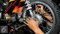 Seorang teknisi tampak memperbaiki roda belakang sebuah sepeda motor, Jakarta, Selasa (14/7/2015). Menjelang H-3 Lebaran, bengkel servis motor di kawasan Pasar Minggu ramai didatangi pengendara yang ingin memperbaiki motornya.(Liputan6.com/Yoppy Renato)