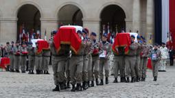 Prajurit  membawa peti jenazah tentara Prancis yang tewas dalam kecelakaan helikopter di Mali, Paris, Senin (2/12/2019). Sebanyak 13 tentara tewas setelah dua helikopter yang ditumpangi bertabrakan dalam operasi melawan miltan di Mali. (AP Photo/Thibault Camus,Pool)
