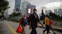 Pekerja berjalan usai bekerja perkantoran di kawasan Jalan Jenderal Sudirman, Jakarta, Kamis (16/4/2020). Pemprov DKI Jakarta akan memberikan saksi berupa mencabut perizinan perusahaan yang tetap beroperasi di masa PSBB kecuali delapan sektor yang memang diizinkan. (Liputan6.com/Faizal Fanani)