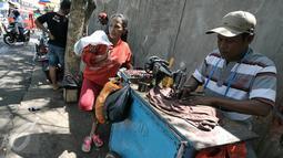 Penjahit keliling memperbaiki pakaian pesanan warga, Jakarta, Senin (4/7/2016). Menjelang hari raya Idul Fitri, penjahit 'vermak levis' keliling mulai kebanjiran rezeki. (Liputan6.com/Yoppy Renato)