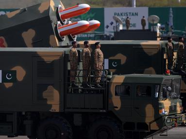 Sejumlah prajurit Pakistan berdiri di samping rudal siluman Babur saat parade Hari Militer Pakistan di Islamabad, Pakistan, (23/3). Parade ini memperingati Resolusi Lahore, perpisahan kaum Muslim dari Kerajaan Britania India. (AFP Photo / Aamir Qureshi)