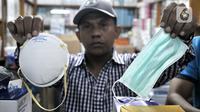 Pedagang menunjukkan masker jenis N-95 (kiri) dan biasa di toko alat kesehatan di Pasar Pramuka, Jakarta, Selasa (4/2/2020). Isu merebaknya wabah virus corona di Indonesia membuat penjualan masker di Pasar Pramuka meningkat pesat meski dalam sepekan harga melonjak tajam. (merdeka.com/Iqbal Nugroho)