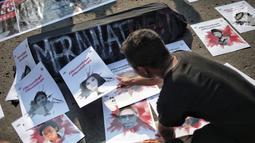 Mahasiswa meletakan poster selama aksi bertajuk #MerawatIngat #MenolakLupa saat car free day (CFD) di Bundaran HI, Jakarta, Minggu (5/5/2019). Aksi tersebut bertujuan untuk mengingatkan bahwa masih banyak kasus-kasus pelanggaran HAM berat yang belum terselesaikan. (Liputan6.com/Faizal Fanani)