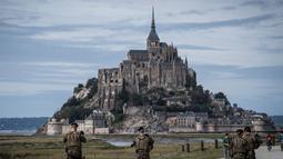 """Tentara """"Sentinelle"""" berpatroli di jalan menuju Mont-Saint-Michel di Normandia, Prancis barat laut (31/8/2019). Jalan akses ke Mont Saint Michel akan terlihat jika air laut surut dan akan hilang saat air laut pasang. (AFP Photo/Joel Saget)"""