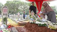 Warga menaburkan bunga di makam Presiden ke-3 RI BJ Habibie yang bersebelah dengan sang istri, Hasri Ainun Besari di TMP Kalibata, Jakarta, Jumat (13/9/2019). Sesuai permintaannya semasa hidup, Habibie dimakamkan bersebelahan dengan mendiang istrinya, Ainun. (Liputan6.com/Herman Zakharia)