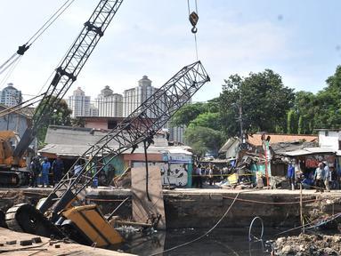 Petugas melakukan evakuasi crane jatuh di kawasan Kemayoran, Jakarta, Kamis (6/12). Crane yang digunakan untuk pembangunan turap Kali Sentiong tersebut jatuh hingga menimpa rumah warga dan menyebabkan tiga orang luka-luka. (Merdeka.com/Iqbal S. Nugroho)