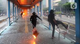 Massa membakar halte Transjakarta di Jalan MH. Thamrin, Jakarta, Kamis (8/10/2020). Aksi anarkis massa dilakukan setelah bentrok dengan petugas kepolisian di kawasan Patung Kuda, Jakarta.(merdeka.com/Arie Basuki)