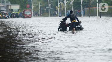 Pengendara mendorong sepeda motor mereka saat melewati banjir yang merendam Jalan Ahmad Yani, Jakarta, Sabtu (8/2/2020). Hujan yang mengguyur Jakarta sejak semalam membuat sejumlah ruas jalan terendam banjir. (merdeka.com/Imam Buhori)