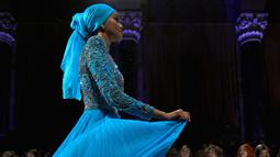 Model Halima Aden berjalan di atas catwalk menggenakan busana rancangan Sherri Hill Show selama New York Fashion Week 2019 di New York City (8/2). Model 21 tahun ini merupakan model pertama yang menggunakan hijab. (AFP Photo/Ben Gabbe)