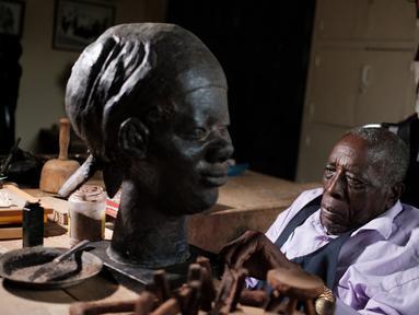 Edward Njenga bekerja memperbaiki patung karyanya yang berjuluk 'Women's Guild Member (2008)' di bengkelnya, Nairobi, Kenya, Senin (12/3). Njenga adalah salah satu pematung terkemuka asal Afrika Timur.  (AFP PHOTO/Yasuyoshi CHIBA)