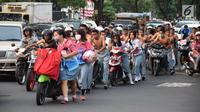 Ratusan pelajar SMA mendorong sepeda motor mereka di Bundaran Simpang Lima, Semarang, Jawa Tengah, Kamis (3/5). Aparat Polrestabes Semarang mengamankan mereka karena mengendarai motor tanpa helm. (Liputan6.com/Gholib)