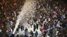 Warga Israel merayakan pelantikan pemerintahan baru di Tel Aviv, Israel, Minggu (13/6/2021). Parlemen Israel telah memberikan suara mendukung pemerintahan koalisi baru yang secara resmi mengakhiri 12 tahun pemerintahan bersejarah Perdana Menteri Benjamin Netanyahu. (AP Photo/Oded Balilty)