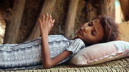 Seorang gadis Yaman yang mengalami gizi buruk terbaring disebuah bangku kayu di desa pesisir yang miskin di pinggiran kota Hodeidah, Yaman (8/4). (AFP Photo/Abdo Hyder)