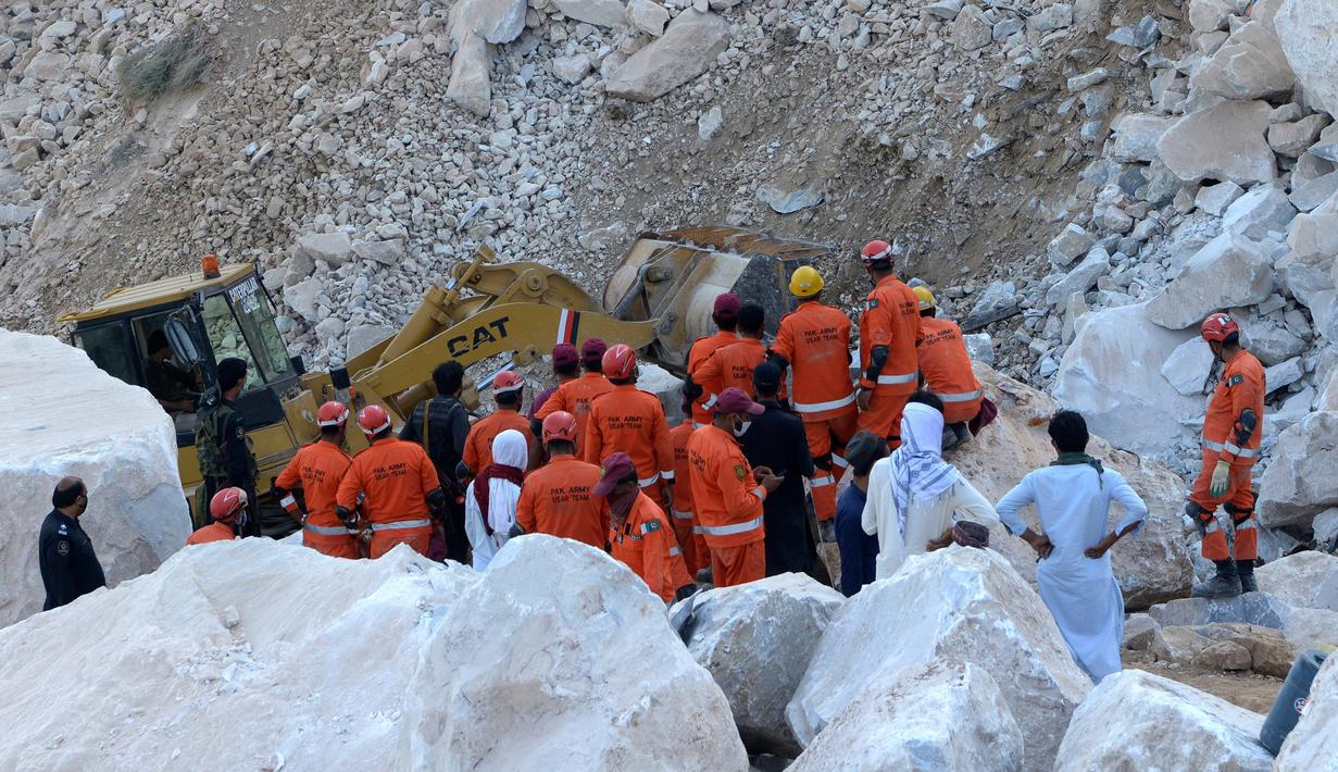 Petugas penyelamat melakukan pencarian korban di lokasi tambang marmer yang longsor di Mohmand, Pakistan, dekat perbatasan Afghanistan, Selasa (8/9/2020).  Sedikitnya 18 penambang tewas dan lebih dari selusin masih terjebak longsor yang terjadi pada Senin (7/9) malam. (AP Photo/Zubair Khan)