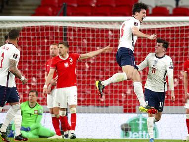 Pemain Inggris Harry Maguire (tengah) melakukan selebrasi usai mencetak gol ke gawang Polandia pada pertandingan Grup I kualifikasi Piala Dunia 2022 di Stadion Wembley, London, Inggris, Rabu (31/3/2021). Inggris menang dengan skor 2-1. (Catherine Ivill, Pool via AP)