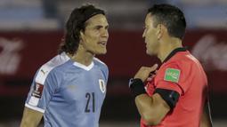 Penyerang Uruguay, Edinson Cavani, berbicara dengan wasit usai diganjar kartu merah saat menghadapi Brasil pada laga lanjutan kualifikasi Piala Dunia zona CONMEBOL di Estadio Centenario, Rabu (18/11/2020) pagi WIB. Brasil menang 2-0 atas Uruguay. (AFP/Raul Martinez/pool)