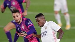 Penyerang Real Madrid, Vinicius Junior  pemain Valladolid, Oscar Plano pada lanjutan La Liga Spanyol di stadion Alfredo, Rau (30/9/2020). Real Madrid menekuk Real Valladolid denga skor 1-0. (AP Photo/Manu Fernandez)