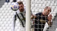 Gelandang Juventus, Aaron Ramsey (kiri) dibayangi bek Genoa, Andrea Masiello melepaskan sundulan ke gawang Genoa dalam laga lanjutan Liga Italia 2020/2021 pekan ke-30 di Allianz Stadium, Turin, Minggu (11/4/2021). Juventus menang 3-1 atas Genoa. (AFP/Marco Bertorello)