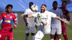 Striker Real Madrid, Karim Benzema, mengontrol bola saat melawan Elche pada laga Liga Spanyol di Stadion Alfredo di Stefano, Sabtu (13/3/2021). Real Madrid menang dengan skor 2-1. (AP/Bernat Armangue)
