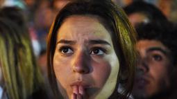 Harap-harap cemas menyelimuti hati seluruh pendukung Aljazair termasuk fans cantik yang satu ini, Senin (30/6/2014) (AFP PHOTO/FAROUK BATICHE)