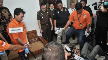 Tersangka Haris Simamora melakukan adegan rekonstruksi pembunuhan keluarga Diperum Nainggolan di Jalan Bojong Nangka, Bekasi, Rabu (21/11). Tersangka pembunuhan satu keluarga di Bekasi itu menjalani 37 adegan rekonstruksi. (Merdeka.com/Iqbal S. Nugroho)