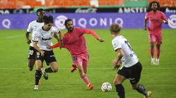 Pemain Real Madrid, Isco, berusaha melewati pemain Valencia pada laga Liga Spanyol di Stadion Mestalla, Minggu (8/11/2020). Valencia menang dengan skor 4-1. (AP/Alberto Saiz)