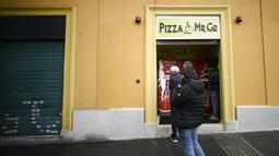Orang-orang mengantre di mesin penjual pizza otomatis, yang pertama dari jenisnya di pusat kota Roma, Italia pada 29 April 2021. Mesin penjual otomatis ini mampu menguleni adonan, membumbui, memasak, dan menyajikan pizza dalam kotak karton hanya dalam waktu tiga menit. (Filippo MONTEFORTE/AFP)