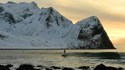 Peselancar menikmati gelombang ombak saat berselancar di pantai bersalju Flackstad di Kepulauan Lofoten, Lingkar Arktik, pada 12 Maret 2016. Suhu laut mencapai 5 derajat celcius dan suhu udara hingga 0 derajat celcius. (AFP/Olivier Morin)