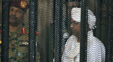Presiden terguling Sudan, Omar al-Bashir ditempatkan di kandang terdakwa selama menjalani persidangan atas dakwaan korupsi di pengadilan di Khartoum, Senin (19/8/2019). Bashir  didakwa dengan tuduhan korupsi, kepemilikan mata uang asing dan menerima gratifikasi. (Ebrahim HAMID / AFP)