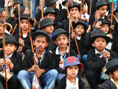 Sejumlah anak berpenampilan seperti Charlie Chaplin berpose memperingati ulang tahun Charlie Chaplin ke-129 di Adipur, sekitar 60 km barat laut Bhuj di negara bagian Gujarat, India barat (16/4). (AFP Photo/Indranil Mukherjee)