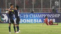 Pemain tengah Timnas Indonesia U-19, M Luthfi Baharsyah (kanan) terduduk usai kalah melawan Jepang U-19 pada perempat final Piala AFC U-19 2018 di Stadion GBK, Jakarta, Minggu (28/10). Indonesia kalah 0-2. (Liputan6.com/Helmi Fithriansyah)