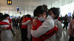 Staf medis dari Provinsi Jilin (merah) memeluk perawat dari Wuhan setelah bekerja bersama menangani pandemi Covid-19 saat upacara pelepasan di Bandara Tianhe, Wuhan, provinsi Hubei, Rabu (8/4/2020). Pemulangan staf medis ini bersamaan dengan dicabutnya status lockdown Wuhan. (Hector RETAMAL/AFP)
