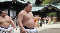 Pegulat sumo Hakuho (depan) dan Kakuryu (kiri) dari Mongolia berjalan dengan para pegulat sumo lainnya setelah berdoa di Kuil Yasukuni di Tokyo, Jepang, Senin (17/4). (AP Photo / Shizuo Kambayashi)