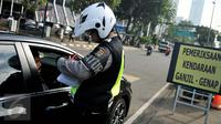 Petugas menilang pengendara mobil berpelat genap yang melintas pada tanggal ganjil di Bundaran Senayan, Jakarta, Rabu (31/8). Sejak kemarin mulai diberlakukan sanksi kepada pengendara yang melanggar aturan ganjil-genap. (Liputan6.com/Gempur M Surya)