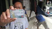 Pedagang menunjukkan Kartu Pedagang di Pasar Induk Beras Cipinang, Jakarta, Rabu (20/11/2019). Dengan Kartu Pedagang, para pedadang akan lebih mudah saat mengajukan kredit ke Bank DKI yang telah terekam dalam sebuah rekening keuangan. (Liputan6.com/HO/Budi)