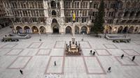 Beberapa orang berjalan melintasi Marienplatz yang hampir kosong selama lockdown di Kota Munich, Jerman, Selasa (5/1/2021). Pemerintah Jerman sepakat untuk memperpanjang langkah-langkah lockdown hingga 31 Januari untuk mengekang penyebaran COVID-19. (Peter Kneffel/dpa via AP)