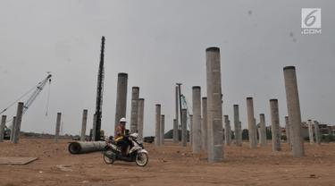 Pekerja melintas di depan tiang pancang proyek Stadion BMW, Jakarta, Rabu (10/7/2019). Di tengah kasus sengketa lahan dengan PT Buana Permata Hijau, PT Jakarta Propertindo (Jakpro) tetap melanjutkan pembangunan Stadion BMW. (merdeka.com/Iqbal S. Nugroho)