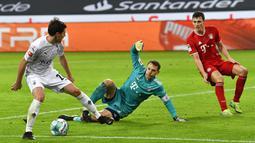Pemain Borussia Moenchengladbach Jonas Hofmann (kiri) mencoba menembak bola di depan kiper Bayern Munchen Manuel Neuer (tengah) pada pertandingan Bundesliga di Borussia Park, Moenchengladbach, Jerman, Jumat (8/1/2021). Bayern Munchen kalah 2-3. (AP Photo/Martin Meissner, Pool)